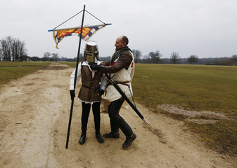 Max Barnes, 12, dressed as a squire, tries wearing a medieval knight's helmet before helping to perform jousts at Knebworth House in Hertfordshire