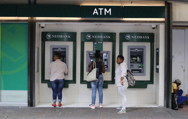 Customers queue to draw money from an ATM outside a branch of South Africa's Nedbank in Cape Town