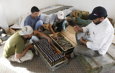 Rebel fighters remove rust from aircraft ammunition near the frontline