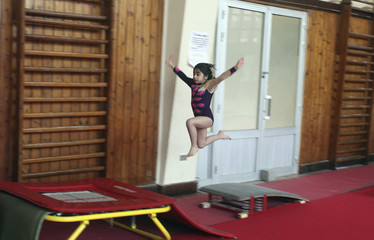 A young girl trains in a gymnastics hall in Alexandria