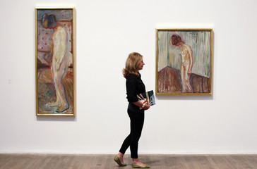 """Ward of the Tate poses with two paintings of Munch's """"Weeping Woman"""" series at the Tate Modern in London's Southbank"""