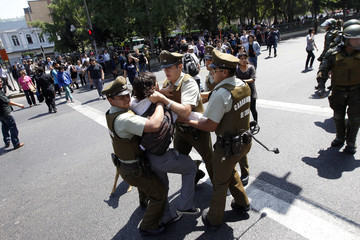 Student protester is detained by riot policemen during a demonstration demanding changes in the public state education system in Santiago