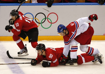 Switzerland's Ambuhl and Josi and the Czech Republic's Jagr chase the puck during the third period of their men's preliminary round ice hockey game at the 2014 Sochi Winter Olympic Games