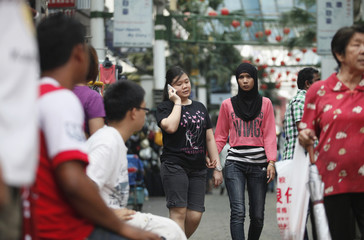 Two women hold hands as they walk along China Town in Kuala Lumpur