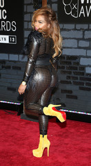 Rapper Lil' Kim poses on arrival at the 2013 MTV Video Music Awards in New York
