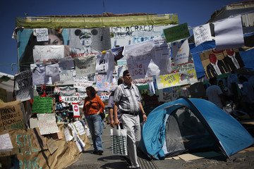 People walk past banners, photos and messages in Madrid's Puerta del Sol