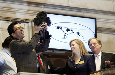 Handler Ernesto Lara holds up Banana Joe, an Affenpinscher, after ringing the opening bell at the New York Stock Exchange