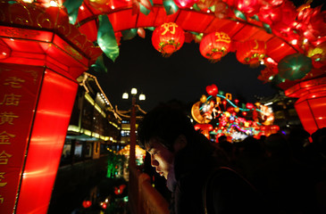 A man walks under Chinese New Year decorations at Yuyuan Garden in downtown Shanghai