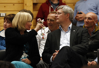 Canada's PM Harper looks on as his wife Laureen displays a gift she received during a community feast in Cambridge Bay