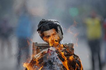 Anti-government protesters burn an effigy depicting Venezuela's President Nicolas Maduro in Caracas