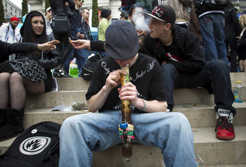 A teenager smokes marijuana out of a bong during the annual 4/20 day, which promotes the use of marijuana, in Vancouver
