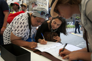 People write their condolence messages for the late former South African President Nelson Mandela in Cape Town