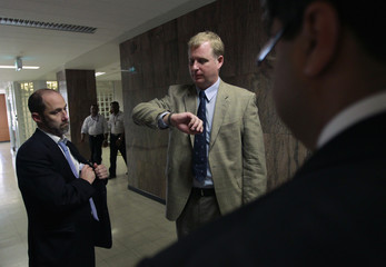 Brian Aitken, outgoing head of the IMF team in Sri Lanka, prepares to leave as the new incoming head Benedict Bingham looks at his watch after a news conference in Colombo