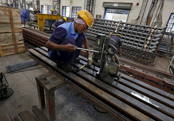 Employees make iron parts which are used to construct bridges inside a manufacturing unit in an industrial area on the outskirts of Kolkata