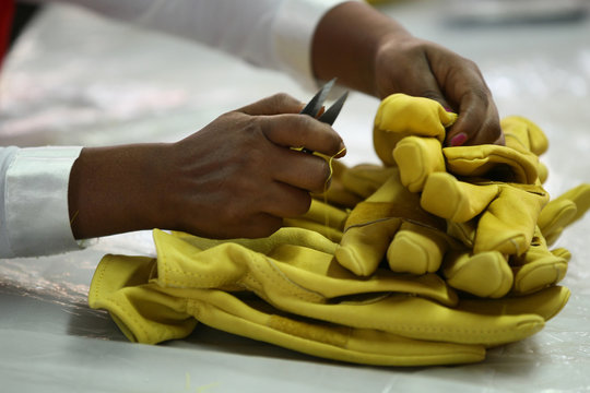 A worker clips an extra strings from a finished working gloves in Pittards world class leather manufacturing company in Ethiopia's capital Addis Ababa