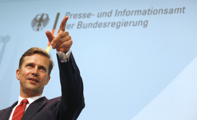 New German government spokesman Seibert gestures as he was introduced into his office by German Chancellor Merkel in Berlin