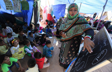 An anti-government protester teaches at a makeshift school, attended by the children of protesters, in front of Parliament House during the Revolution March in Islamabad