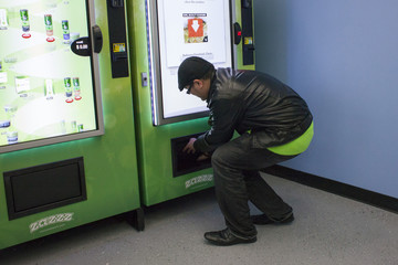 A man uses a ZaZZZ vending machine to purchase one gram of the Girl Scout Cookies strain of marijuana for $15 at Seattle Caregivers in Seattle