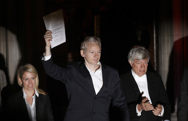 WikiLeaks founder Julian Assange celebrates as he emerges to speak to the media on the steps of the High Court, in London