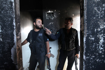 Members of Sheikh Ali Khatib battalion talk to each other inside a burnt house near Hanano Barracks in Aleppo