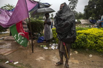 An anti-government protester covers himself with a sheet of plastic during heavy rain in the morning, in front of the President's house in a Red Zone, during the Revolution March in Islamabad