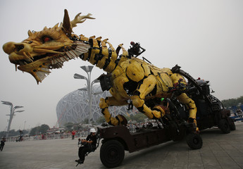 "A mechanical installation named ""Long Ma"" is operated in front of the National Stadium in Beijing"