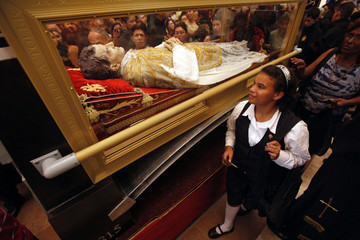 Catholics walk past a wax replica of St. John Bosco at the Metropolitan Cathedral in Tegucigalpa