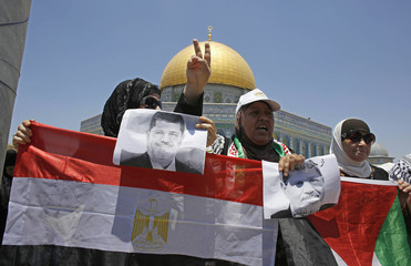 Palestinian women hold pictures of ousted Egyptian President Mursi during pro-Mursi demonstration before prayers in Jerusalem's Old City