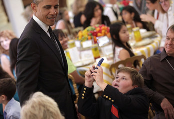 "A boy takes pictures of U.S. President Obama at ""Kids' State Dinner"" in Washington"