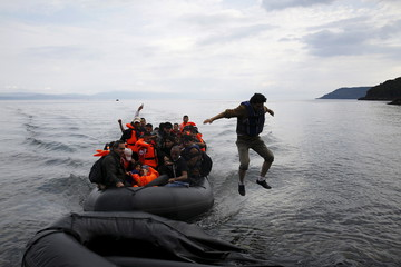 Migrant jumps off a dinghy upon arriving on the Greek island of Lesbos