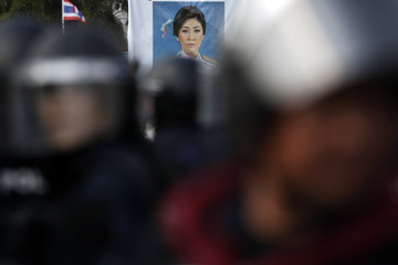 A picture of Thai Prime Minister Yingluck Shinawatra is seen behind riot policeman as they move into anti-government encampment near the Government House in central Bangkok