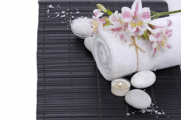 In de dag Spa Spa setting with candle, towel ,orchid, ,salt in bowl on mat
