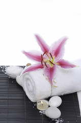 Tuinposter Spa Spa setting with candle on towel ,stones .lily on mat