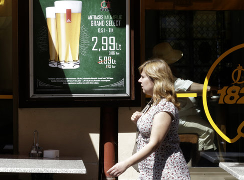 A woman walks past a pizza shop with a price list in Lithuanian litas and euros, in Vilnius