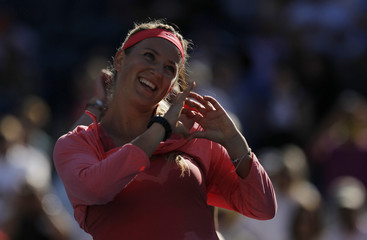 Azarenka of Belarus makes a heart symbol as she celebrates defeating Pennetta of Italy at the U.S. Open tennis championships in New York