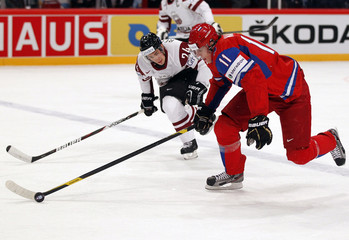 Russia's Malkin is challenged by Latvia's Redlihs during their 2012 IIHF ice hockey World Championship game in Stockholm