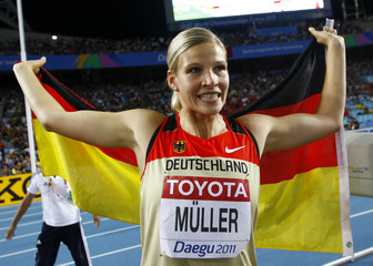 Muller of Germany holds her national flag after winning the silver medal during the women's discus throw final at the IAAF World Championships in Daegu