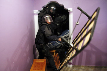 Spanish riot police enter the apartment of Montoya Vazquez past pieces of furniture stacked up against the door to carry out her family's eviction in Madrid