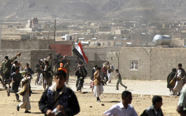 Anti-government protesters run during clashes with supporters of Yemen's outgoing President Ali Abdullah Saleh near Sanaa