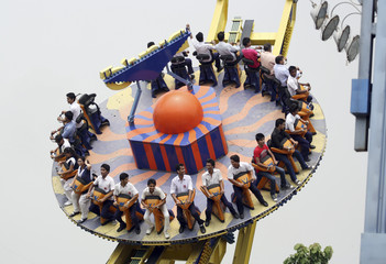 Visitors ride the Mega Disco roller coaster at an amusement park in Noida