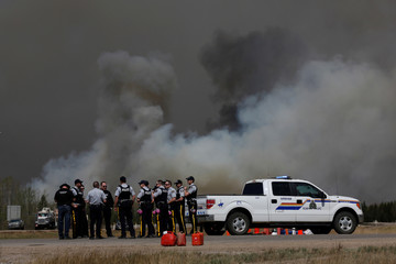RCMP talk as smoke rises from a wildfire south of Fort McMurray