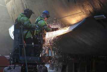 Workmen weld part of the hull of the Royal Yacht Britannia as it sits in a dry dock at Forth Ports in Edinburgh