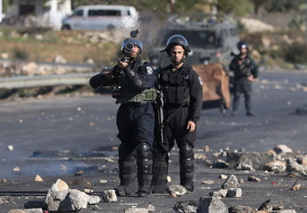Israeli border policeman fires a tear gas canister towards Palestinian protesters during clashes near the Jewish settlement of Bet El, near Ramallah