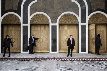 Kazakh and American bodyguards wait as U.S. Secretary of State John Kerry tours the Hazrat Sultan Mosque in Astana