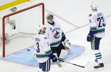Vancouver Canucks' goalie Roberto Luongo reacts after giving up a goal to the Boston Bruins as his teammates Kevin Bieksa and Alexander Edler look on during the second period in Game 3 of the Stanley Cup hockey playoff in Boston