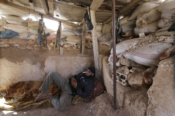Free Syrian Army fighter rests on one of the front lines of Wadi Al-Daif camp in the southern Idlib countryside