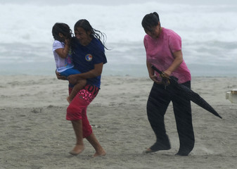 Beach goers get caught in a squall as feeder bands from Hurricane Irene begin to pound Atlantic Beach