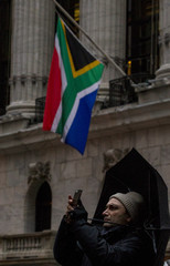 A man takes a photo as the South African flag hangs at half-mast, in honor of the death of former South African President Mandela, outside the New York Stock Exchange