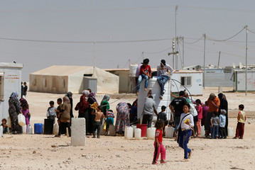 Syrian refugees collect water at the Al-Zaatari refugee camp in Mafraq, Jordan, near the border with Syria