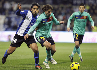 Barcelona's Messi and Hercules' Aguilar fight for the ball during their Spanish first division soccer match in Alicante